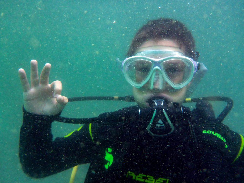 Jeune Plongeur PADI Qui Maîtrise Les Signes Sous L'eau